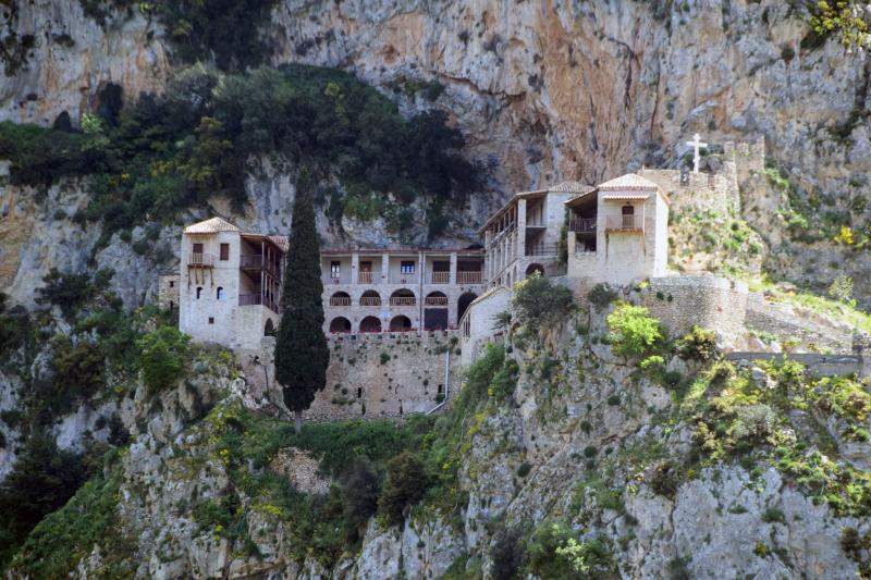 A monastery nestled into the base of rising cliffs